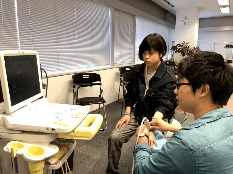 超音波画像診断装置のセミナーで、装置の使い方を練習する長尾先生と小俣先生の写真