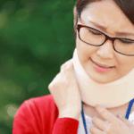 むち打ちによる頚部痛で顔をしかめる女性